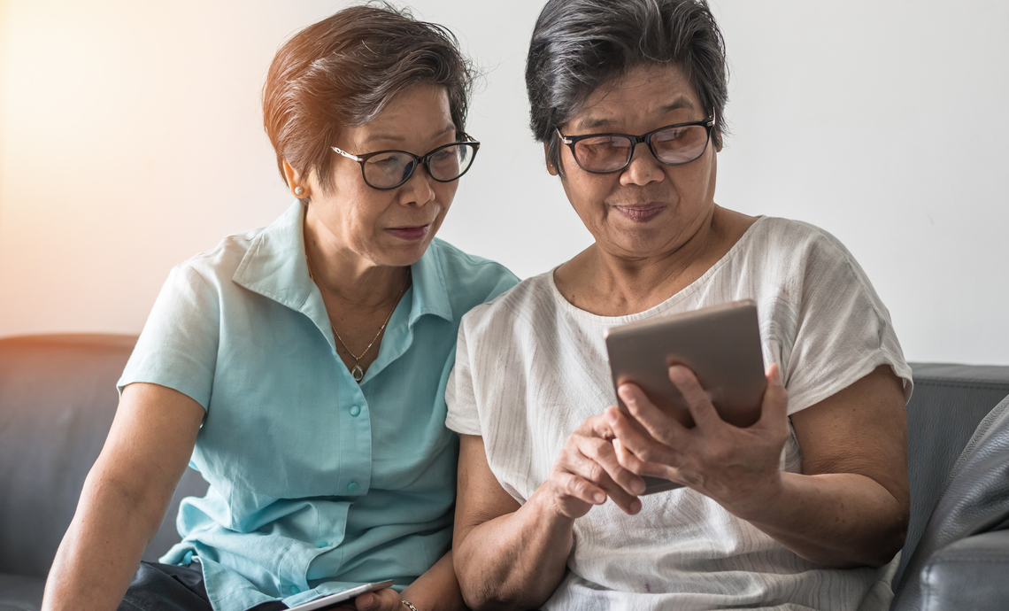 Same-gender older couple sitting on a couch and looking at a tablet together.